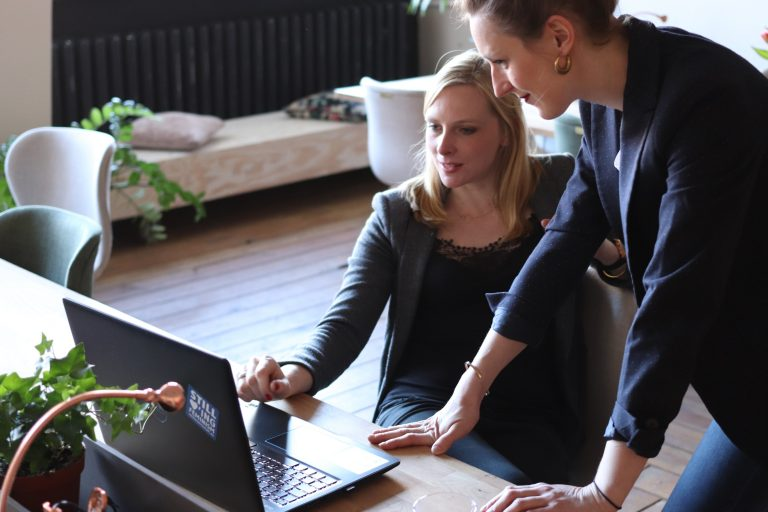 Two business women looking at a laptop