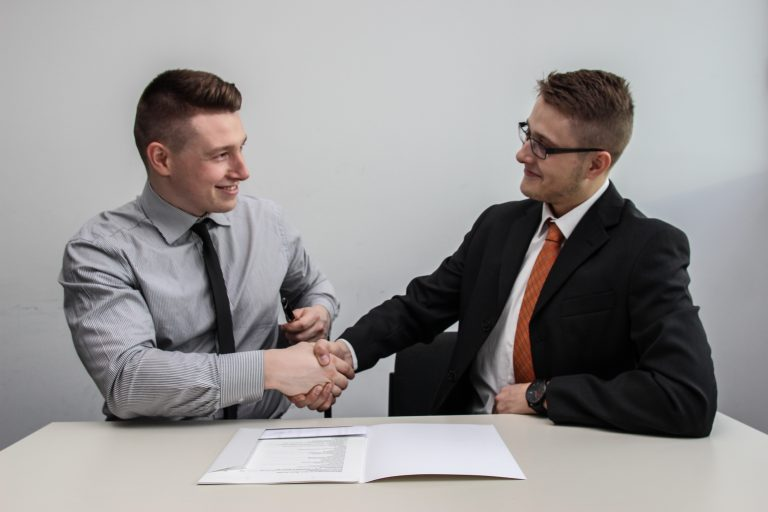 two men shaking hands over a document