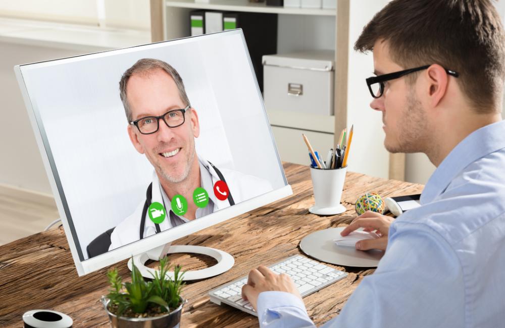 man speaking to doctor via telehealth