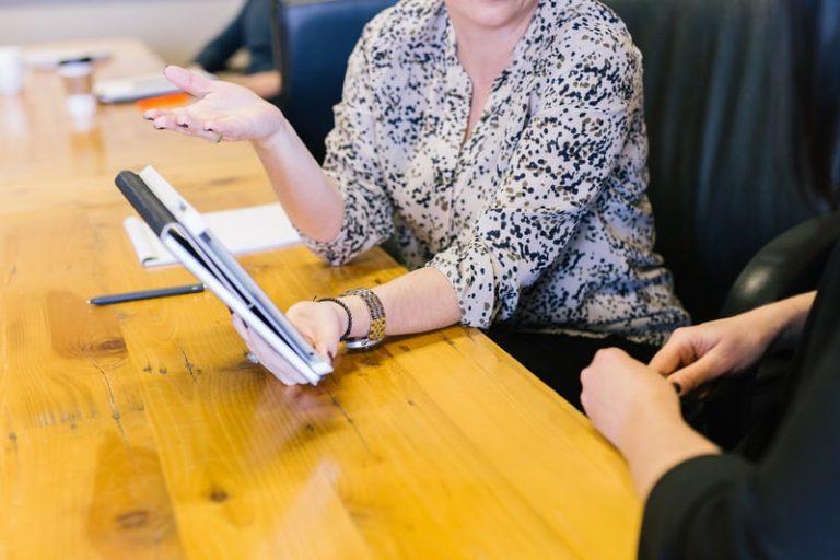 women showing coworker info on a tablet